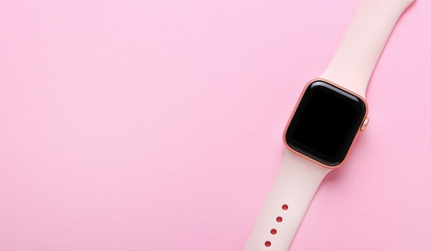 Close up pf pink woman smart watch on the pink background.flat lay,top view.smart modern technologies.