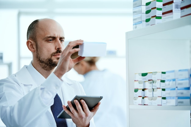 Close-up. pharmacist is reading the information on the screen of his digital tablet.