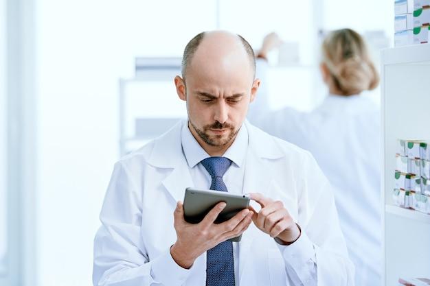 閉じる。職場でデジタルタブレットを使用している薬剤師。