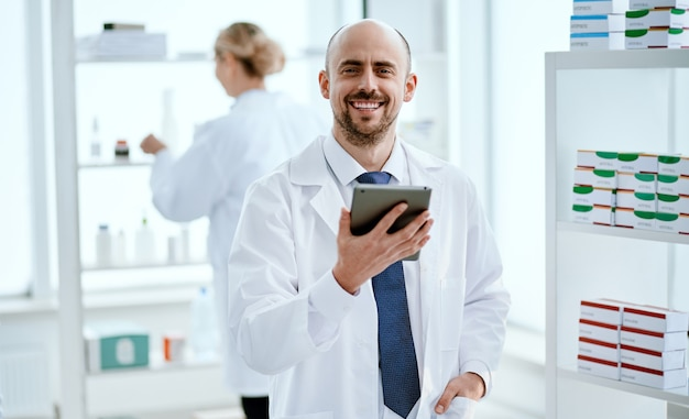 Close-up. pharmacist with a digital tablet looking at you.