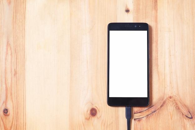 Закройте телефон и кабель для передачи данных для передачи и зарядки аккумулятора на фоне деревянного пола и использование текстуры для концепции технологии