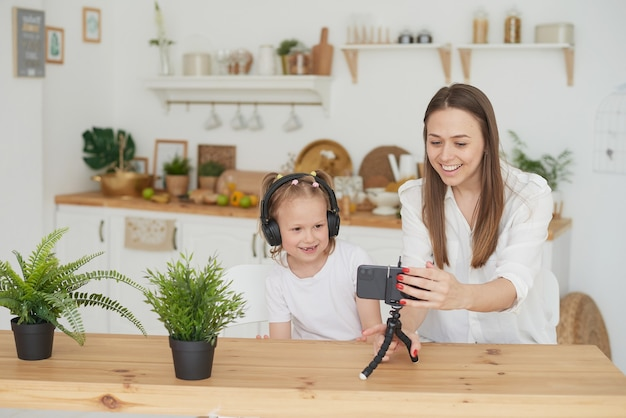 Close-up of a phone on a tripod on the kitchen table. happy mom and daughter sit at the table in the kitchen and record educational videos for vlogging.