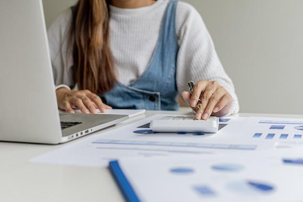 클로즈업 사진 한 여성의 손이 계산기를 누르고 있고, 회의 요약을 가져오기 전에 정확성을 확인하기 위해 계산기를 사용하여 문서를 계산합니다. 금융 개념입니다.