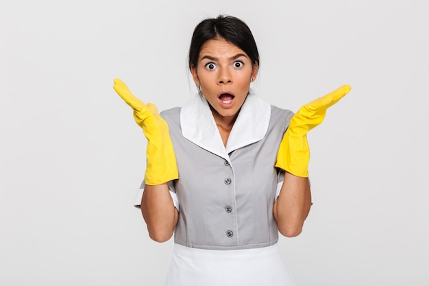 Close-up photo of amazed young female housekeeper in uniform and protective gloves standing with opened palms