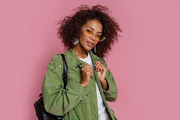 Close up photo of amazing curly african girl on pink background. wearing green trendy jacket.