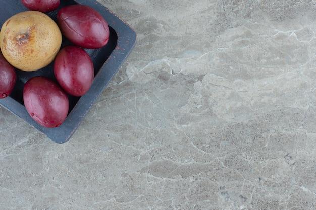 Chiuda sulla foto della mela e delle palme sul piatto di legno grigio.