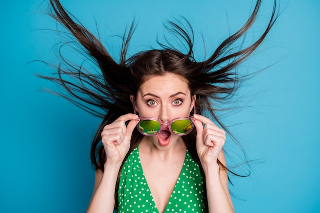 Close up photo of astonished girl touch hand specs impressed news information novelty wind blow air hairstyle wear good look clothes isolated over blue color background