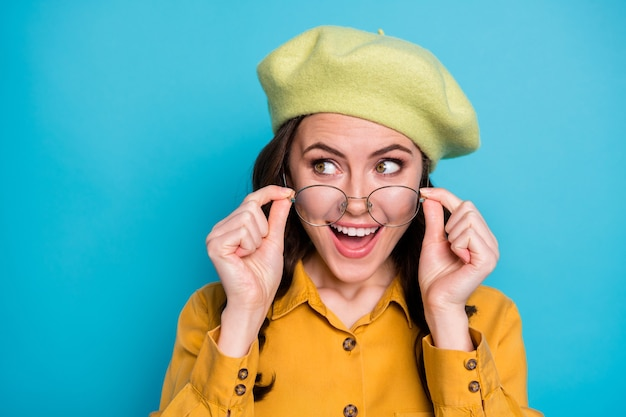 Close up photo of astonished positive cheerful girl look copyspace touch specs impressed season bargain information wear yellow shirt headwear isolated over blue color background