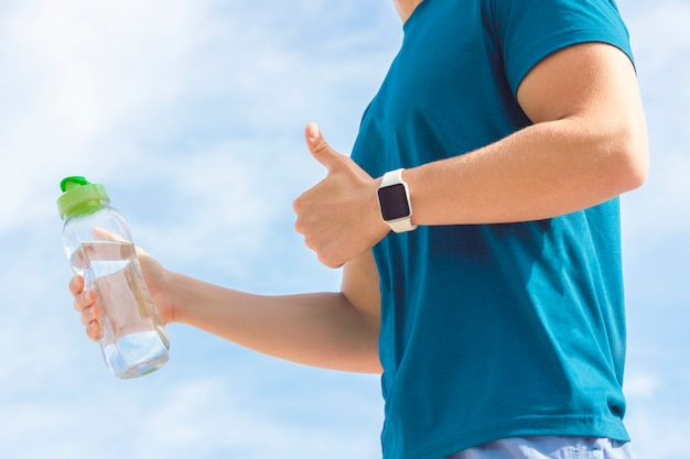 Close up photo of athlete's hand with smartwatch, bottle of water in hand. unrecognizable person, fit man runner showing like gesture, thumb up. healthy sport active fitness lifestyle, gadget concept