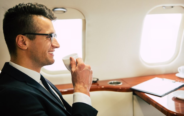 Close-up photo of an attractive man in business clothes, who is drinking coffee and having a small talk with his colleague on his business strip, while flying first class.