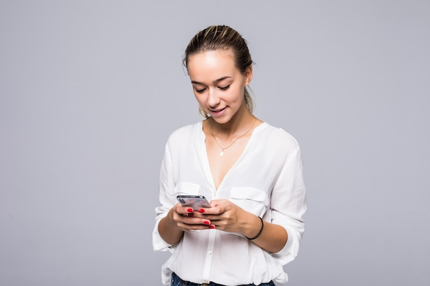 Close up photo of attractive smiling girl standing against gray wall and typing sms on her smartphone