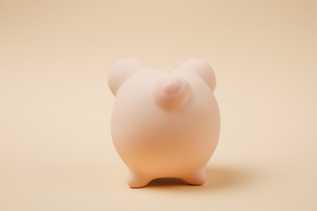 Close up photo, back rear view of pink piggy money bank isolated on beige wall background. money accumulation, investment, banking or business services, wealth concept. copy space advertising mock up.