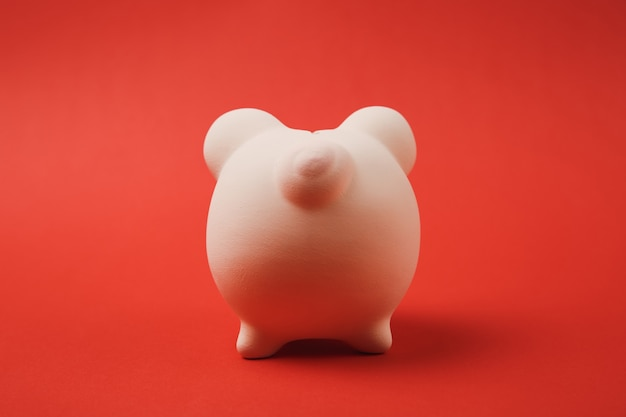 Close up photo, back rear view of pink piggy money bank isolated on red wall background. money accumulation, investment, banking or business services, wealth concept. copy space advertising mock up.