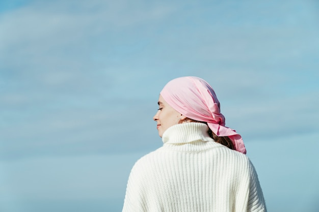 Close up photo of back view of young woman with cancer looking to left on the coast