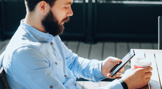 Close up photo of bearded businessman having a coffee break while surfing on mobile