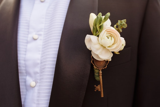 Close up photo of beautiful boutonniere decorated with key on the groom's black jacket.