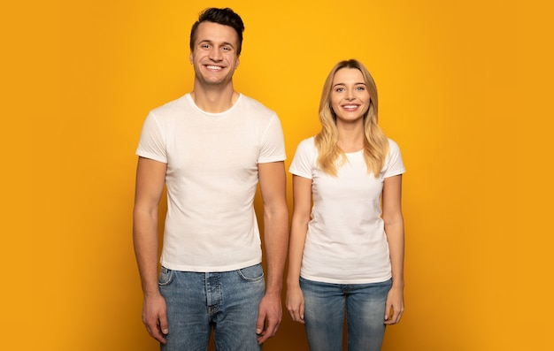 Close-up photo of a beautiful couple, who are posing in white t-shirts on a yellow background with their arms down, looking in the camera and smiling.