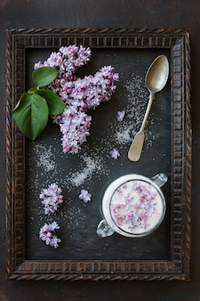 Close-up photo of beautiful fresh lilac flowers in sugar in frame on black table. top view