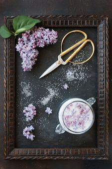 Close-up photo of beautiful fresh lilac flowers in sugar and vintage scissors in frame on black table. top view