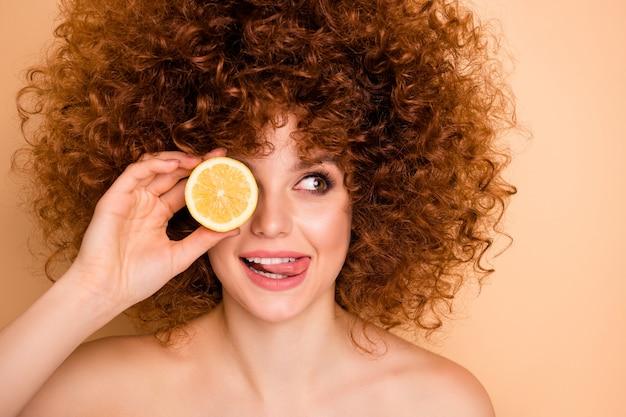 Крупным планом фото красивая дама скрывает глаза за ломтиком лайма лимона языком изо рта