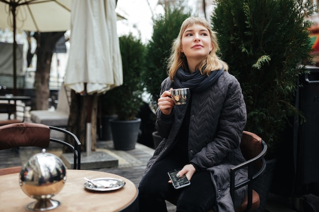 Close up photo of beautiful lady sitting at the table on street and drinking coffee