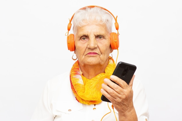 Close up photo of beautiful senior caucasian woman with headphones isolated over grey background