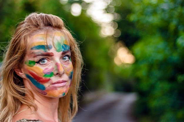 Close-up photo of beautiful woman with colorful painted face