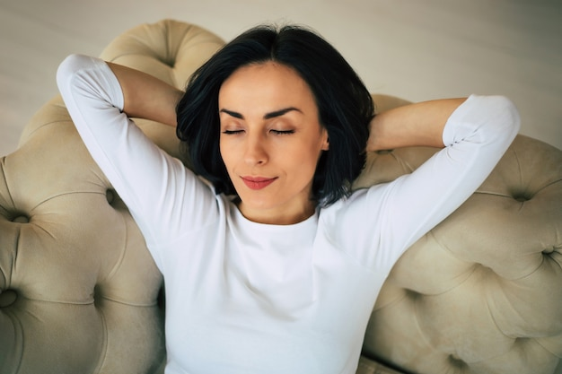 Close-up photo of a beautiful woman with short black hair who is laying on her sofa with her hands behind her head and dreaming about her success in a big city.