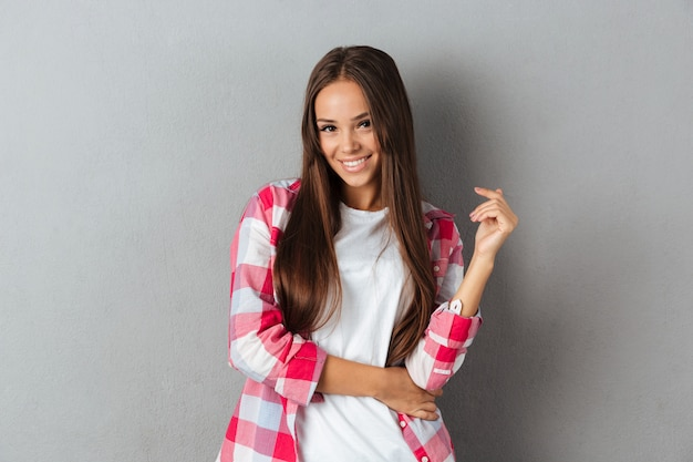 Close-up photo of beautiful young brunette woman in checkered shirt isolated