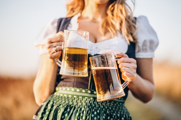 Close-up photo of blonde in dirndl, traditional festival dress, holding two mugs of beer in her hands