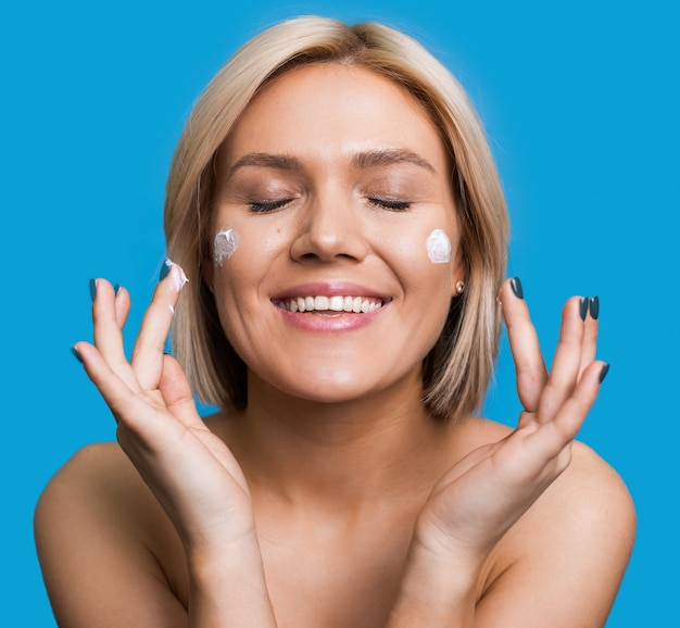 Close up photo of a blonde lady with naked shoulders applying a cream on her face posing on a blue studio wall
