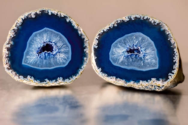 Close up photo of a blue agate mineral on a reflective surface. agate has a typical zoned structure and is visible even to the naked eye.