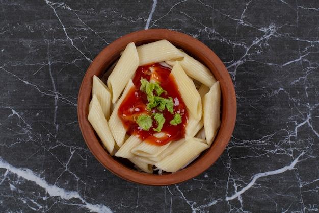 Primo piano foto di pasta di penne bollita con salsa ketchup in una ciotola di ceramica.