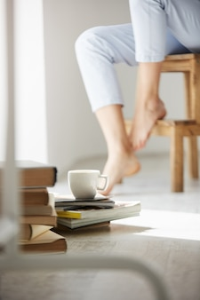 Close up photo of books and cup of coffee lying on floor. woman's legs on chair.