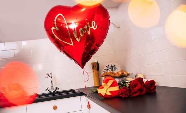 Close-up photo of a bouquet of red roses, a big balloon and a red heart-shaped box with a golden ribbon, which lie on a kitchen table.