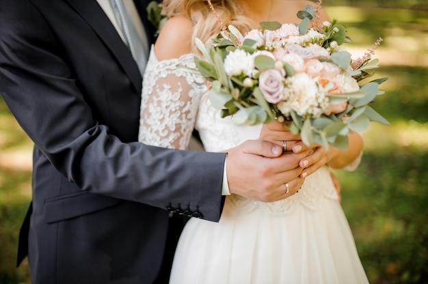 Close up photo of a bridegroom embracing a bride