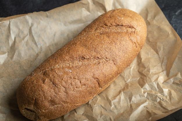 Close up photo 영국 블루머 종이 배경에 배턴 로프 빵입니다.