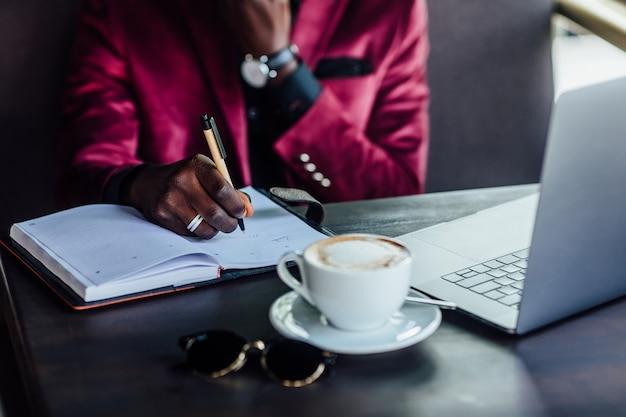 写真をクローズアップ。カフェショップでメモを書くビジネスマン。ビジネスコンセプト。