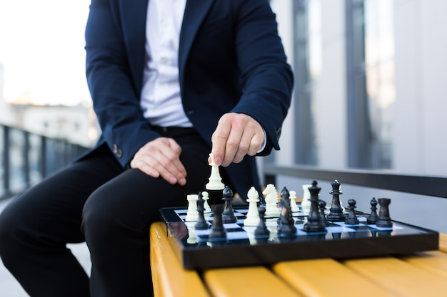 Close-up photo of businessman's hands making a move on a chessboard, male businessman playing chess
