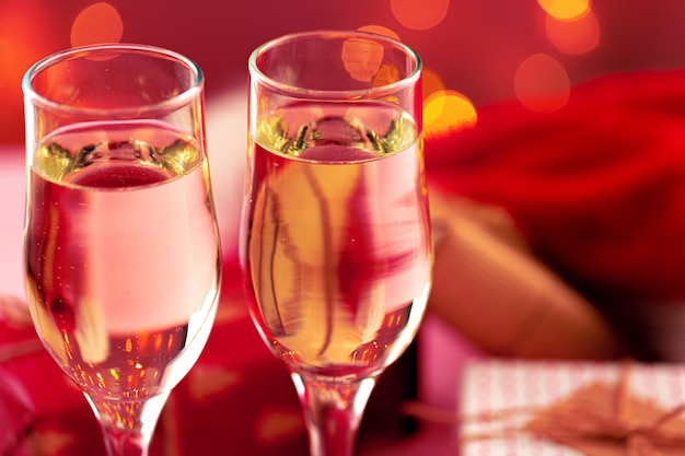 Close up photo of champagne glasses against bokeh lights background