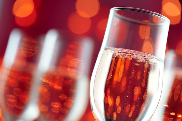 Close up photo of champagne glasses against bokeh lights