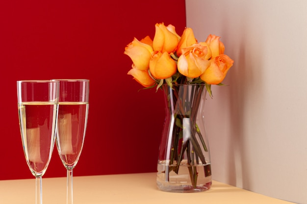 Close up photo of champagne glasses with roses in a vase