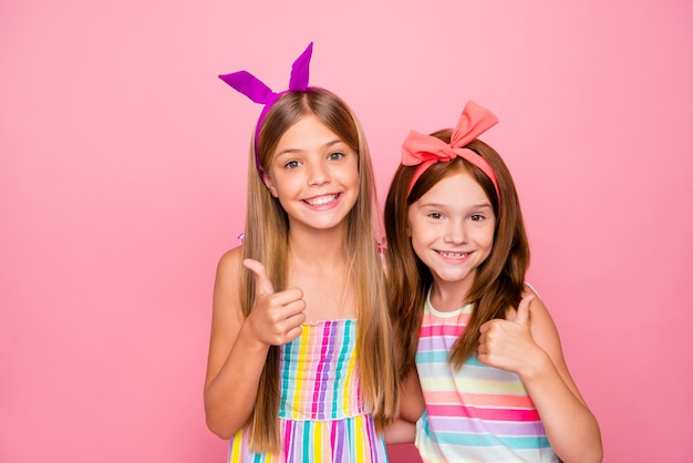 Close up photo of charming kids hugging embracing showing thumb up wearing bright headbands skirt dress isolated over pink background