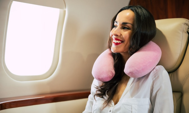 Close-up photo of a charming lady in a white blouse, who is taking a nap in her window seat on business class aircraft.