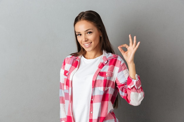 Close up photo of cheerful young brunette woman showing ok gesture