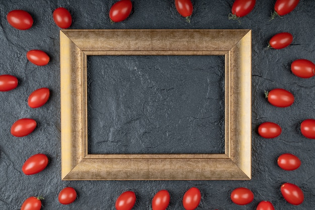 Close up photo of cherry tomatoes around golden frame on black background. high quality photo
