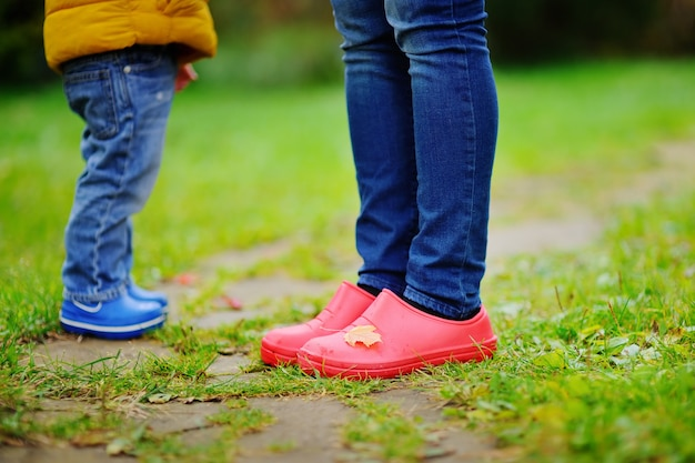 Close up photo of child and adult legs in rubber boots. family in autumn.