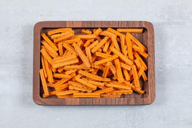 Primo piano foto di patatine sul piatto di legno.