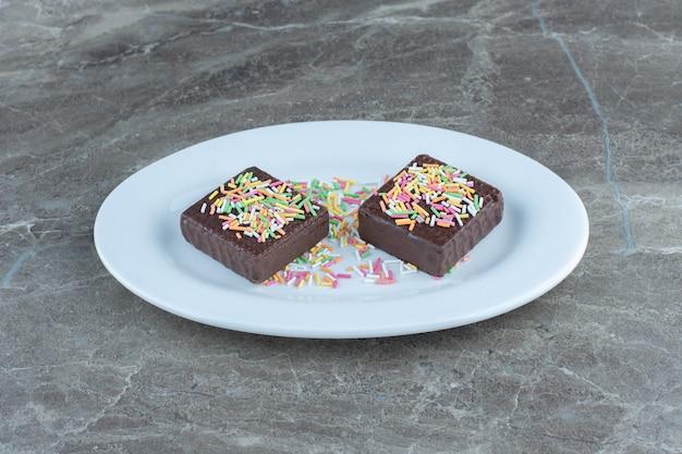 Foto ravvicinata di wafer al cioccolato su piatto in ceramica bianca.