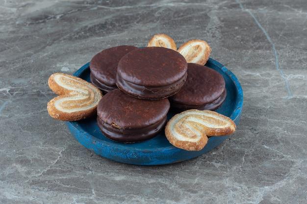 Foto ravvicinata di wafer al cioccolato con biscotti fatti in casa su piatto di legno blu.